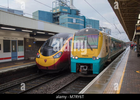 Two different generation Alstom manufactured trains at Warrington Bank Quay. On the left is a Class 390 Pendolino - Stock Photo