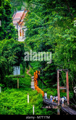 Kanchanaburi, Thailand - September 15, 2012: Buddhist monks marching on wooden bridge to get back to the church - Stock Photo