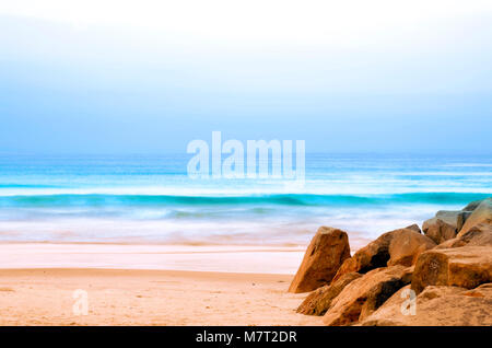 Relaxing calm day at the beach with soft ocean waves rolling onto the golden sandy beach. - Stock Photo