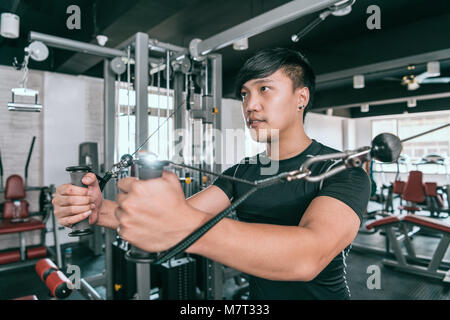 Man working out in gym doing cable standing fly on tower. Exercise for the muscles of the chest. - Stock Photo
