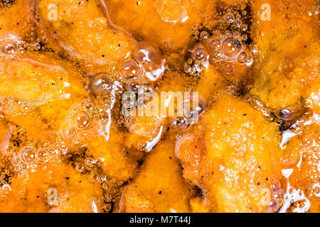 Frying the meat wrapped in breadcrumb on the pan, close up. Fried chicken in oil. - Stock Photo