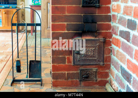 view of the stove and accessories close-up in a wooden country house close-up - Stock Photo