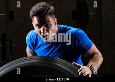 close-up portrait of a screaming sportsman bodybuilder lifting a heavy large wheel - Stock Photo