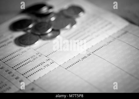 Savings account bank book showing money about and coins on the book - Stock Photo