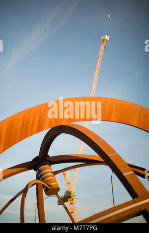 bright orange rusty sculpture with yellow tower crane and daylight moon in the background - Stock Photo