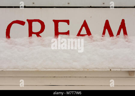 Red and white sign saying cream with ice and snow in background - Stock Photo