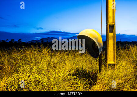 Public phone booth in a vacant lot at evening. Florianopolis, Santa Catarina, Brazil. - Stock Photo