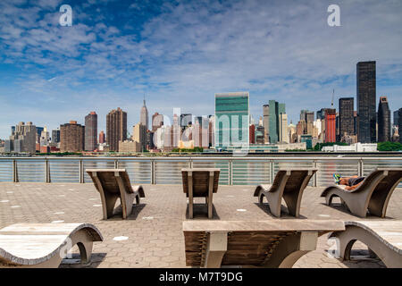 Man sunbathing on a wooden sun lounger in Gantry Plaza State Park , Long Island City across the East River from - Stock Photo