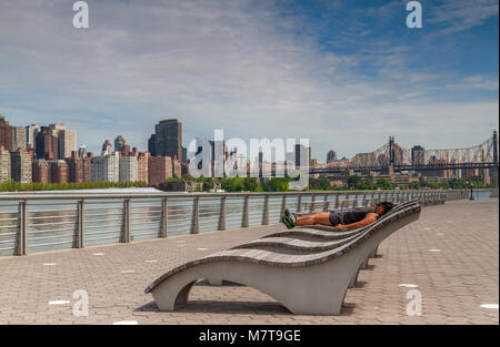 Man sunbathing on a wooden sun lounger in Gantry Plaza State Park across the East River from Manhattan with the - Stock Photo
