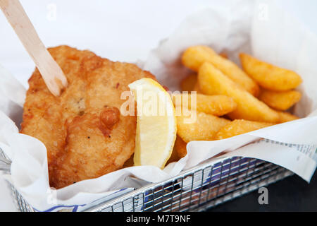 Fish and chips, with a chip fork in a metal basket. - Stock Photo