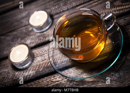 A Cup Of Tea With 2 Tealights On Old Wooden Floorboards - Stock Photo