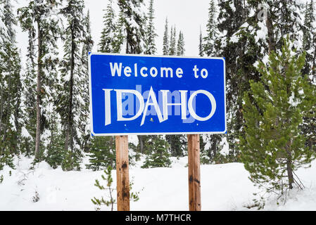 Idaho welcome sign with snow falling in winter on road at Lost Trail Pass in Bitterroot Mountains, Idaho, USA - Stock Photo