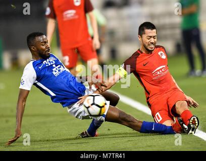 (180313) -- DOHA, March 13, 2018 (Xinhua) -- Osama Hawsawi (L) of Al-Hilal FC vies with Rodrigo Tabata of Al-Rayyan - Stock Photo