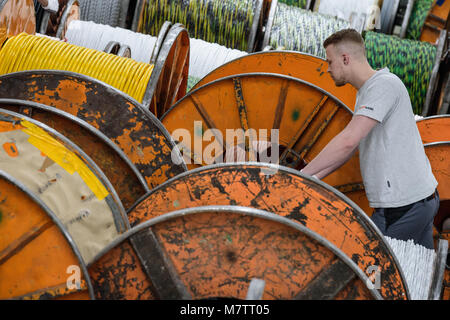 08 March 2018, Germany, Stuttgart-Vaihingen: An employee of the cable producer Lapp works on rolled up cables. Lapp - Stock Photo