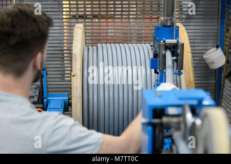 08 March 2018, Germany, Stuttgart-Vaihingen: An employee of the cable producer Lapp supervises the rolling up of - Stock Photo
