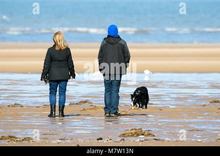Southport, Merseyside. 13th March 2018. UK Weather.  A dog walker heads down onto the beach as the sunshine finally - Stock Photo