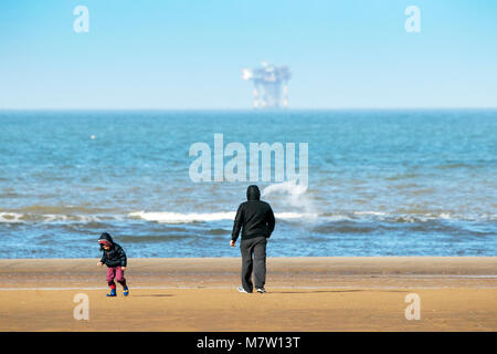 Southport, Merseyside. 13th March 2018. UK Weather.  A father plays with his son on the beach as the sunshine finally - Stock Photo