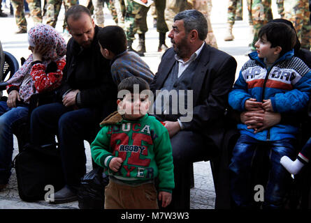 (180313) -- DAMASCUS, March 13, 2018 (Xinhua) -- Evacuated Syrian civilians wait at a temporary shelter in Wafidin - Stock Photo