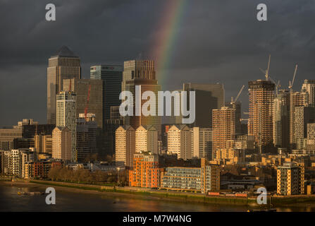 London, UK. 13th March, 2018. UK Weather: A rainbow breaks over Canary Wharf business park buildings in east London - Stock Photo