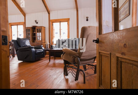 Living room inside the extension of an old Canadiana cottage style fieldstone residential home. - Stock Photo