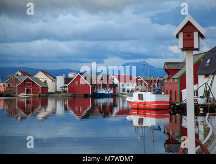 Waterfront wooden buildings and fishing boats reflecting in the water at the port of Kalvaag - a small village in - Stock Photo