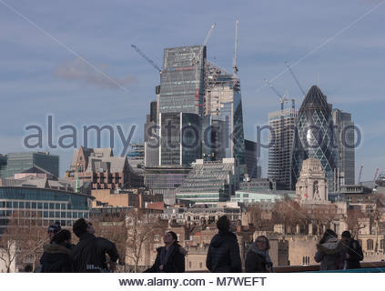 Tourists walking over Tower Bridge. Behind them is a view of The City of London. - Stock Photo
