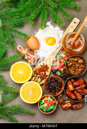 Prepare a fruitcake. The ingredients on the table - dark and light raisins, dates, flour, eggs, honey, cinnamon, - Stock Photo