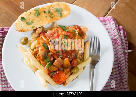 A portion of Italian style Chicken Cacciatore served with penne pasta and Garlic bread. - Stock Photo