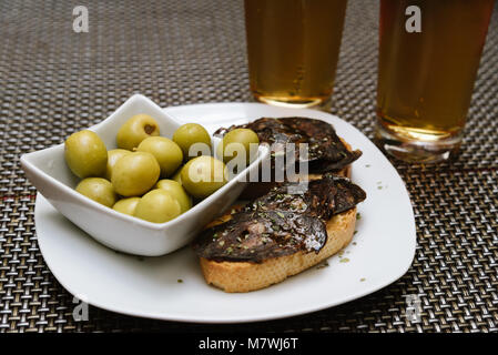 Spanish tapa set with olives and chorizo, a  spicy Spanish pork sausage, on bar table. - Stock Photo
