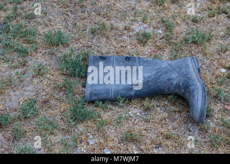 Discarded single dirty rubber gumboot isolated on an outdoors background image in landscape format with copy space - Stock Photo