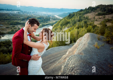Adorable cheerful newlyweds are hugging at the background of the lovely landscape. The emotional wedding portrait. - Stock Photo
