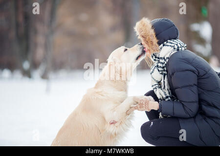Picture of girl hugging labrador in snowy park - Stock Photo