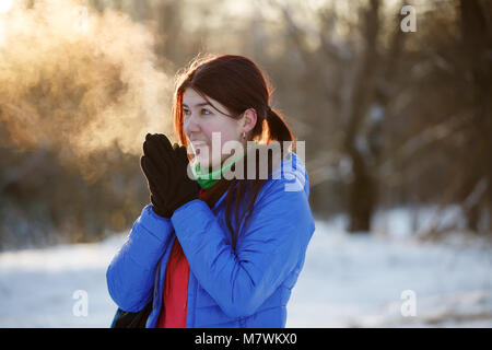 Picture of sporty woman warming her hands in winter forest
