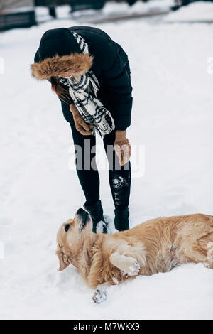 Image of girl in black jacket with retriever on walk in winter park - Stock Photo