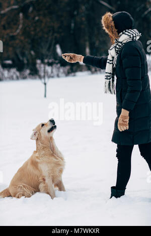 Picture of woman playing with dog in winter park - Stock Photo