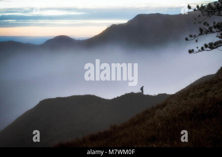 Man lost in the clouds in the mountain - Stock Photo