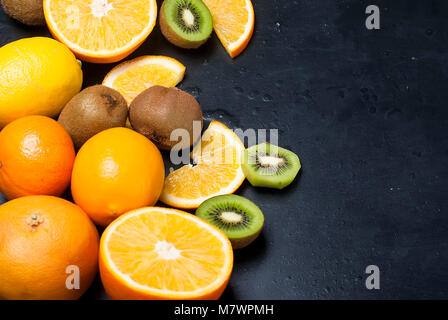 Variety of fresh citrus fruits on dark background from slices of kiwi and orange ,copy space - Stock Photo