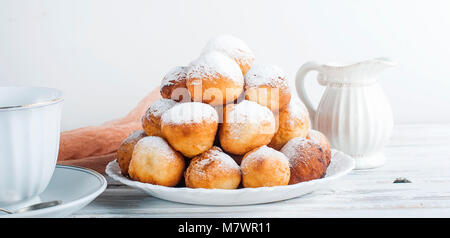sweet donuts laid out pyramid sprinkled with powdered sugar on the plate , Milk jug and cup, breakfast , copy space - Stock Photo