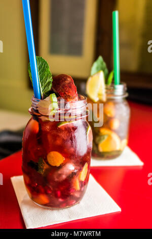 Homemade lemonade ice tea colorful icetea drink with fresh sweet fruits mint leaves in glass on the rocks with a - Stock Photo