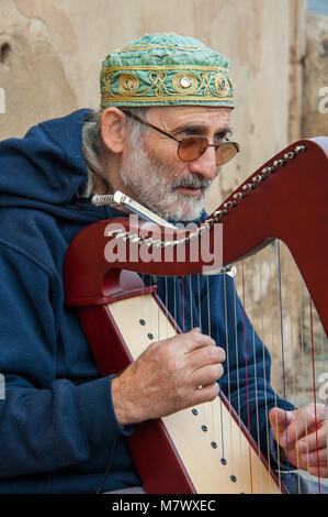 Close up of musician playing a harp at Prague Castle. Man with beard wearing green fez, blue jacket plays traditional - Stock Photo