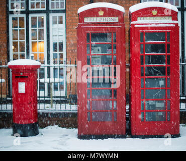 Typical British red pillar post box and telephone box covered in snow during blizzard - Stock Photo