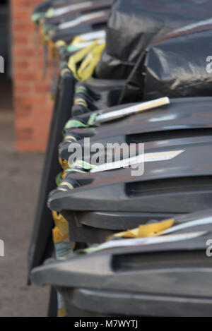 row of grey UK wheelie bins in a line with wall in background - Stock Photo