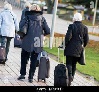 middle aged women in rush with flight bags after missing plane end up being lost and walking through park - Stock Photo
