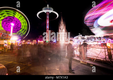 ghostly people at funfair in town centre with motion blur - Stock Photo