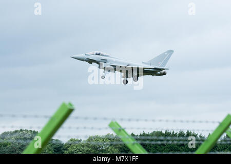 Eurofighter typhoon on landing approach with barbed wire fence in foreground. - Stock Photo