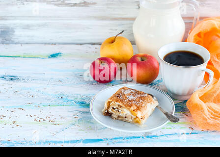 Sweet roll with apple on a plate with sugar cup of black coffee and a jug of milk, apples for breakfast - Stock Photo