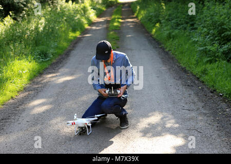 Generic illustration on the theme of civilian drone (unmanned aerial vehicles). Drone pilot preparing his equipment - Stock Photo