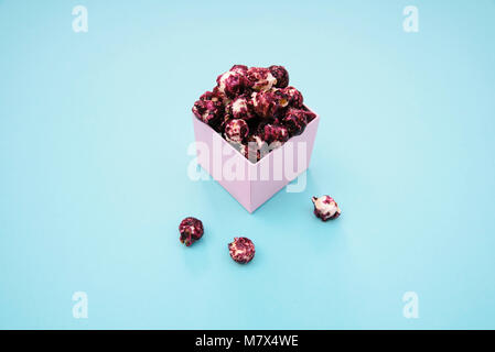 Pink popcorn with berry taste in paper cup on blue background. - Stock Photo