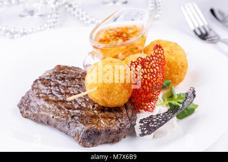 Beef steak with an appetizing garnish of potato balls. Close-up. - Stock Photo