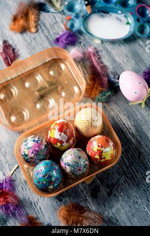 closeup of some homemade decorated easter eggs in a plastic egg box, and some other easter eggs on a gray rustic - Stock Photo